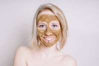 young woman with healing earth or clay beauty facial mask
