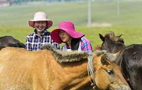 Zwei junge mongolische Frauen mit modischen Hüten zwischen Pferden