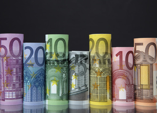 Rolled up Euro bills on dark background