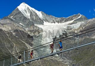 Wanderer überqueren die Charles Kuonen Hängebrücke vor dem Weisshorn Gipfel, Randa, Wallis, Schweiz