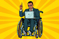African businessman in wheelchair with laptop