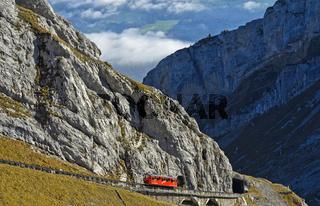 Roter Wagen der Pilatusbahn auf der steilen Bahnstrecke am Pilatus Bergmassiv,Alpnachstad, Schweiz