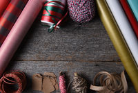 Top view of Christmas present wrapping supplies on a rustic wood table with copy space.