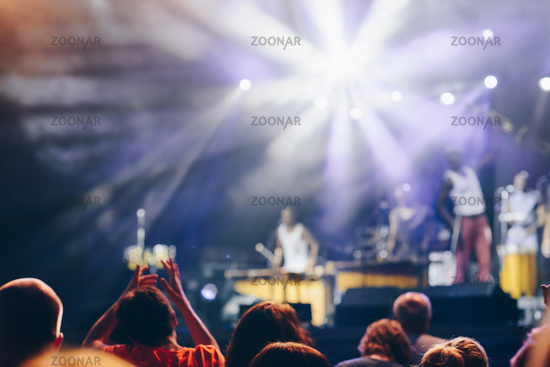 Blurred Crowd at concert of unrecognizable music group and blurred stage lights