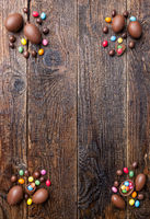 Delicious chocolate Easter bunny and eggs on wooden background