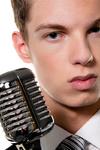 Junger  Sänger mit Retro Mikrofon singt Karaoke