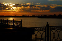 Beautiful sunset on the river metal fence of embanlment silhouette