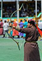 Weiblicher Bogenschütze in traditioneller Deel-Kleidung