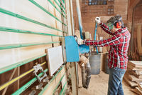 Schreiner sägt in Werkstatt Holz