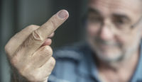 A laughing senior shows the stinky finger.