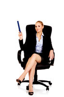 Young business woman sitting on armchair and pointing up with big pen