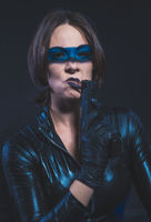 Secret agent, Brunette girl dressed in leather and latex fitted with pistol on blue background