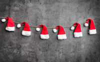 Traditional Christmas Santa hats on rustic background with copy space
