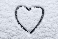heart shape in snow on car window -