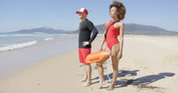 Female and male lifeguards posing on beach