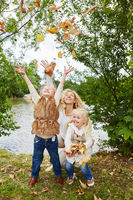 Kinder werfen Blätter in die Luft