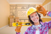 Female Construction Worker Holding Level In Front of Custom Built In Entertainment Unit Drawing in Empty Room.