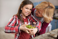 Granddaughter with grandmother mixing salad in the kitchen.