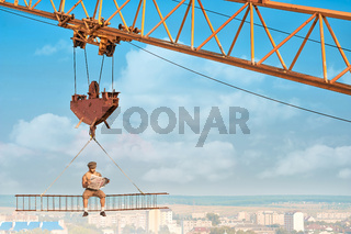 Crane holding iron construction, where sitting builder.