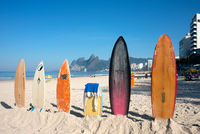Surfboards standing upright in bright sun on the Ipanema beach