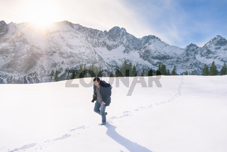 Man walking through snow in mountains