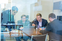 Relaxed cheerful business people sitting and talking at corporate meeting.