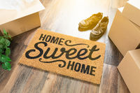 Home Sweet Home Welcome Mat, Moving Boxes, Shoes and Plant on Hard Wood Floors