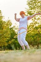 Aktive Seniorin trainiert Fitness mit Reifen