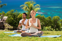 happy couple doing yoga and meditating outdoors