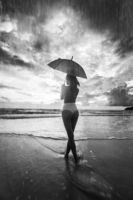 Beautiful woman with umbrella on the beach