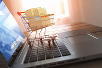 Shopping online and e-commerce. Laptop and shopping cart with boxes on laptop keyboard,