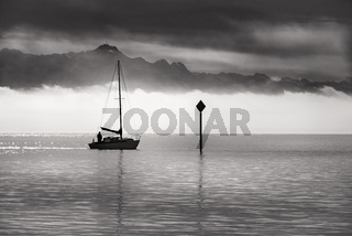 Monochrome image of a single boat sailing