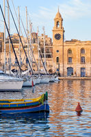 Traditional maltese boat (Luzzu) and yachts moored in the harbor in front of Malta Maritime Museum.