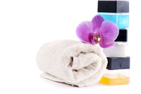 Stack of spa accessories with flower and towel
