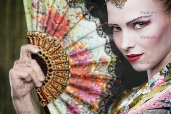 Beautiful young woman as geisha with fan