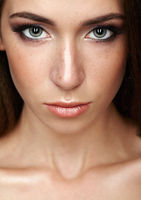 Closeup beauty portrait of young woman. Brunette girl with long hair and day female makeup