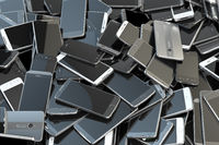 Heap of different smartphones. Mobile phone technology concept background.