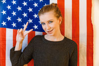 Hipster girl make victory sign in front of US flag