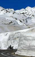 Motorradfahrer fährt auf der Passtrasse zwischen hohen Schneemauern über den St. Gotthardpass