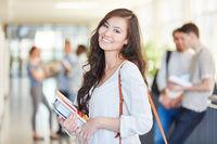 Glückliche asiatische Studentin in der Uni