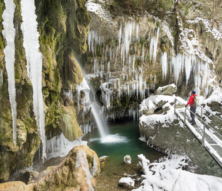 Traveler man enjoying icicles and waterfall on cold winter hike. Hinanger Waterfall, Bavaria, Germany