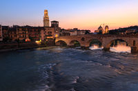 Verona cityscape with Ponte Pietra on Adige river with historical buildings in the evening