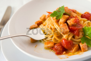 Closeup of spaghetti with fish and little tomatoes