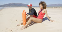 Male and female lifeguards sitting on beach