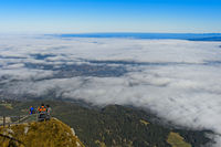 Tourists looking from Mount Pilatus at the partially cloud-covered city of Lucerne, Switzerland