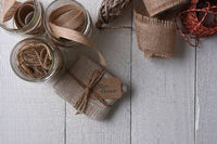 Top view of a burlap wrapped Christmas present on a rustic wood table with twine and ribbon. Horizon