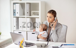 businesswoman with baby calling on phone at office