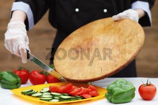 The cook cuts fresh farm vegetables