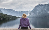 Woman wearing purple hoodie watching tranquil overcast morning scene at lake Bohinj, Alps mountains, Slovenia.