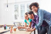 Lachende Studentin mit Kollegen am Laptop